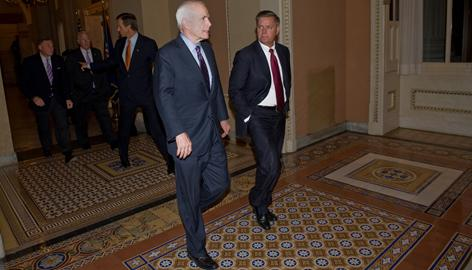Republican presidential candidate Sen. John McCain speaks with Sen. Lindsey Graham as he walks back to the Senate chamber to vote on the financial bailout plan Wednesday night on Capitol Hill. The Senate approved the bill 74-25.