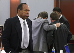 "O.J. Simpson is shown during his armed-robbery trial as co-defendant Clarence ""C.J."" Stewart confers with his attorneys in the background at the Clark County Regional Justice Center Wednesday in Las Vegas."