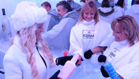 Bartender Melanie Markham, left, serves up drinks for guests inside ICEBAR Orlando where guests drink vodka from glasses made of ice in 27-degree temperatures.