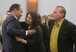 "O.J. Simpson embraces his sister Carmelita Durio as his friend Tom Scotto looks on in court after a guilty verdict was reached late Friday at the Clark County Regional Justice Center in Las Vegas. Simpson and co-defendant Clarence ""C.J."" Stewart were found guilty on all charges."