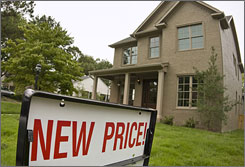 A sale sign sits in front of a home in an older neighborhood of Little Rock, last August. Experts believe home prices must stop falling for the financial rescue to work.
