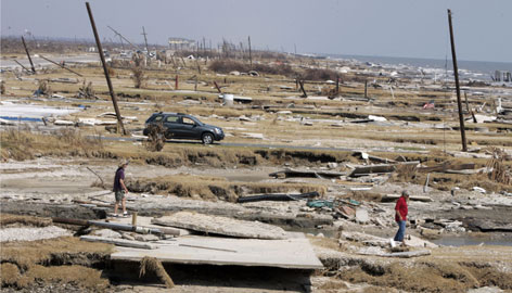 People make their way over the debris-strewn beach in Gilchrist, Texas Sept. 26 when residents of the seaside community on Bolivar Peninsula were allowed to return home.
