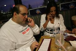 At La Cigale, a Dearborn, Mich., restaurant specializing in Middle Eastern cuisine, Haidar Abdallah, 31, of Dearborn, left, and Hayat Jaber, 30, of Livonia, Mich., make calls to drum up interest in Barack Obama.
