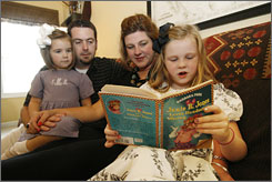Sadie, from left, Blake and Stephanie Morgan listen to Molly, 6, read a Christian children's book in Murfreesboro, Tenn.