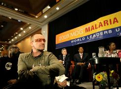 Musicians Youssou N'Dour, left, and Bono listen to speakers at the United Nations 2008 Millennium Development Goals Malaria Summit in New York on Sept. 25.