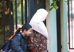 A French schoolgirl is accompanied by her veiled mother at the gate of a school in the Paris suburb Aubervillers in September 2004. Such a headscarf would be acceptable under a new French rule because it is not a burqa covering the body and face.