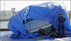 The wreackage of a 26-foot Bayliner pleasure boat used by Henry Sanchez and Penny Avila is covered with a tarp after being recovered from the ocean floor in the Los Angeles harbor by the U.S. Coast Guard on Thursday.