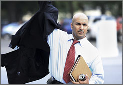 Treasury Department Assistant Secretary Neel Kashkari puts his jacket on as he arrives at the Dirksen Senate Office Building on Capitol Hill in Washington.