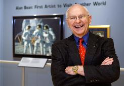 "Artist Alan Bean, the fourth man to walk on the moon, shows off a preview of his work at the Lyndon Baines Johnson Library and Museum on Oct. 1 in Austin, Texas. ""They're not like Earth paintings,"" he said. ""They're paintings from another world."""