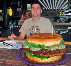 Brad Sciullo of Uniontown, Pa., ate a 15-pound cheese burger, pictured, with five-pounds of toppings including bun, lettuce, tomatoes, cheese, onions, mild banana peppers and a cup each of ketchup, mustard, relish, and mayonnaise at Denny's Beer Barrel Pub in Clearfield, Pa., Monday. Sciullo finished the concoction in 4 hours and 39 minutes.