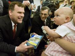 Canadian Environment Minister John Baird, left, and Health Minister Tony Clement hand out baby bottles that are free of the chemical BPA to 5-month-old Georgia Symonds and other babies in April.