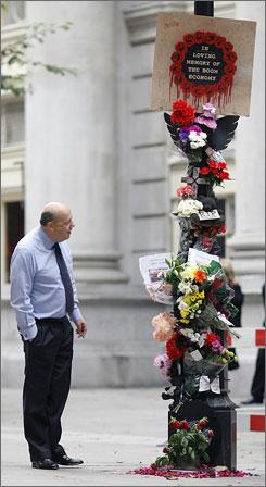 A passerby appreciates street art lamenting the death of London's boom.