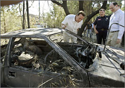 California Gov. Arnold Schwarzenegger examines damage Thursday in the Twin Lakes area of Los Angeles County from the Sesnon Fire.