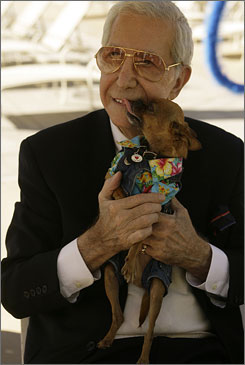 """Seen here in Oct. 2006, Richard Blackwell, also known as Mr. Blackwell, gets a kiss from his declared best dressed dog winner, during an event promoting """"Dine With Your Dog Day"""" in Los Angeles. Blackwell died Sunday of complications from an intestinal infection."""