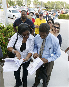James and Shirley Walker check their sample ballot as they wait in line Monday at the Plantation, Fla., library to cast their early ballot. They stood in line over an hour to vote.
