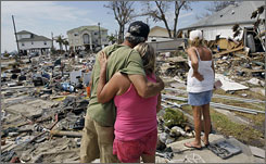 Wayne Neill and Brenda Roby hug as Donna Hanson looks at her lost Galveston, Texas, home last month.