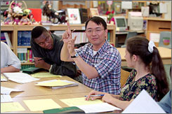 A growing teacher shortage is forcing many U.S. school districts to recruit from foreign countries. Shown here are teachers George Lampley, left, of Ghana, Wen Kang Chein of Taiwan and Anna Olech of Poland talking about their students at a seminar at Cesar Chavez Multicultural Academic Center in Chicago in June 2001.