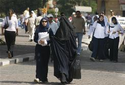 An Egyptian woman, right, wears a niqab -- a veil which shows only the eyes -- as she walks with another, wearing a hijab, or headscarf, in downtown Cairo.