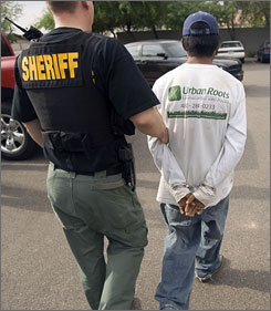 A Maricopa sheriff?s deputy detains Armando Garcia, 18, in June in Mesa, Ariz. Garcia admitted to not having the proper identification to be in the country after his vehicle was stopped for expired tags. He was sent to a processing center.