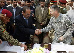 The United States has handed over control of Babil province to Iraq. Here, Babil Gov. Salem al-Saleh Melmawe, left, shakes hands with U.S. Maj. Gen. Michael Oates, right, on Monday after signing the official transfer of power.