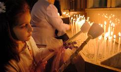 Alyssa Karavitis, 7, lights her candle before going into church on Greek Orthodox Easter at Holy Trinity Greek Orthodox Church in Bridgeport, Conn., in 2005.