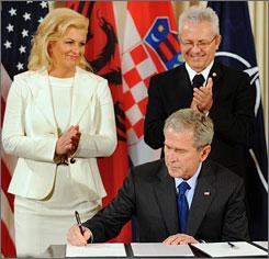 Croatian Ambassador to the U.S. Kolinda Grabar-Kitarovic, left, and Albanian Ambassador to the U.S. Aleksander Sallabanda, right, watch as President Bush signs NATO accession protocols for the two countries, Friday.
