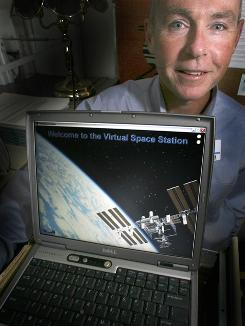 "Dartmouth psychologist Dr. Mark Hegel poses in his office Oct. 24 with his laptop in Lebanon, N.H. Hegel is working on a computer program, ""The Virtual Space Station,"" that will guide astronauts through treatment for depression and other problems while in space."