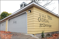 The FBI says that vandalism found on the homes of four legislators in Minnesota did not amount to a federal crime. Here, graffiti is seen on the garage of the St. Paul home of Sen. Norm Coleman, R-Minn., on Wednesday.