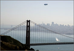 The Air Ventures Zeppelin flies over the Golden Gate Bridge to complete its cross-country transit flight with the San Francisco skyline in the background on Saturday. The airship, one of only three currently flying anywhere in the world, is the first Zeppelin to fly in the skies over the U.S. in 71 years.