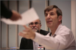 Stephen Spitz, background, watches Thursday as elections board worker Dave Alvino hands out an absentee ballot.