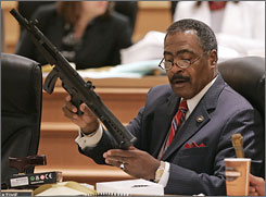 Rep. John DeBerry, D-Memphis, displays a toy gun that looks like the real thing during a committee meeting in Nashville, Tenn., Thursday, May 1.