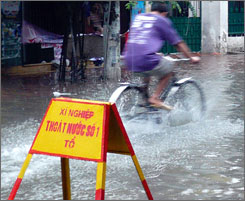 A bicyclist rides through a flooded street in Hanoi, Vietnam, on Saturday.