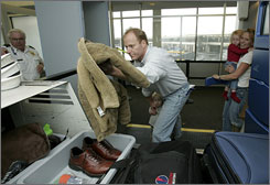 David Neaderland throws his jacket into an airport checkpoint bin in Newark.