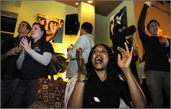 Patrons watching the election results come in cheer for Barack Obama in a Washington, D.C. restaurant.