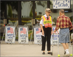 Security guard Carol Cahill, left, helps direct a voter to the polls at a community center in Deerfield, Fla., Tuesday.