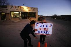 Election poll workers Connie Ortega, left, and Carol Hite set up a sign Tuesday in front of the Apache Drums general store in La Madera, N.M. The site serves a northern New Mexican community with a population of 150 people.