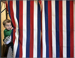 Eighteen-month-old Jaeden Kittoe peeks out of the curtain as his mother, Michelle, votes at the Wrightstown American Legion on Election Day in Wrightstown, Wis.
