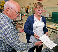 Poll worker Rex Guice assists Kayla Phillips with placing her ballot in a voting machine in Laramie, Wyo. John McCain became the 11th straight Republican presidential candidate to win the state's three electoral votes.