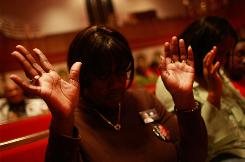 A woman wearing an Obama pin prays during a Southern Christian Leadership Conference rally in the historic Sixteenth Street Baptist Church the day before Election Day in Birmingham, Ala.