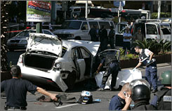 Israeli police inspect the scene of an explosion in Tel Aviv on Monday that they believe killed a top organized crime figure there.