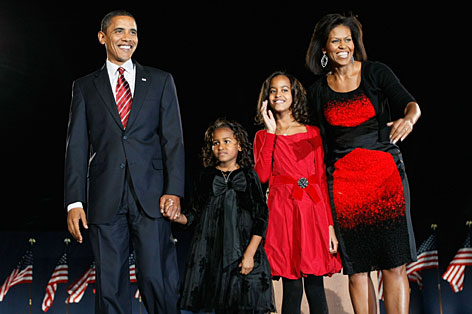 U.S. President elect Barack Obama stands on stage along with his wife Michelle and daughters Malia (red dress) and Sasha (black dress) during an election night gathering in Grant Park, Tuesday, in Chicago.