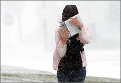 A student shields her face from snow and wind in whiteout conditions on the campus of Bismarck State College in Bismarck, N.D.