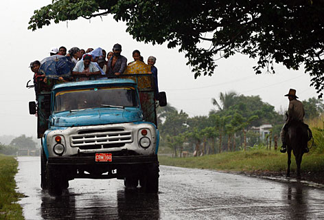 People leave their home aboard the back of a truck in search of shelter as Hurricane Paloma approaches in Santa Cruz del Sur, Camaguey, Cuba, Saturday.