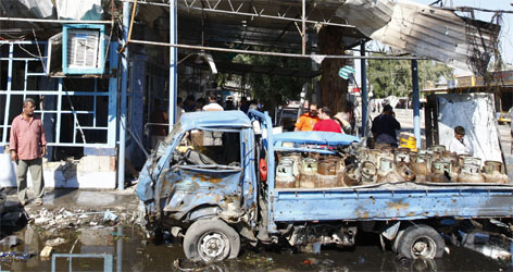 A damage truck loaded with liquefied petroleum gas tanks lies on a street after a triple bomb attack in Baghdad's Kasra neighborhood Monday.