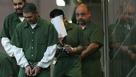 Shawn Nguyen, shown covering his face, leaves the courthouse in Houston on Feb. 14, 2006. The former federal air marshal was sentenced to seven years in prison.