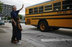 Esteban Ricardo, with his son Ricky Ricardo, 4, waves as his other five children take the school bus from the front of the Homeless Assistance Center where they live in Miami.