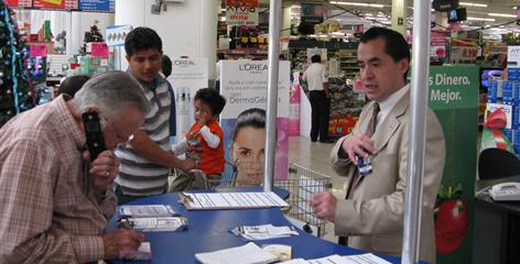 Leopoldo Benitez, right, tries to sign up customers for a Wal-Mart credit card at a store in Mexico City on Thursday.