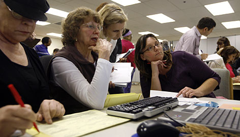 Election workers, from left, Carolyn DiPaul and Nancy Marx; Jennifer Allen of the Begich campaign, and Kim Chatman confer about a ballot Tuesday.
