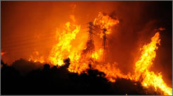 Flames cross over a ridge occupied by high-voltage power lines near Mountain Drive and Coyote Road in Montecito, Calif. on Thursday. A brush fire destroyed homes in the tiny enclave of Montecito, forcing evacuations as gusting winds pushed the blaze further into the community that has long been a hideaway for the rich and famous.