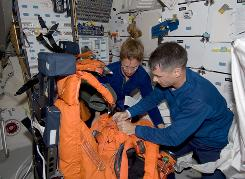 Astronauts Shane Kimbrough, right, and Sandra Magnus work with their shuttle launch and entry suits after launch on the space shuttle Endeavour on Friday.